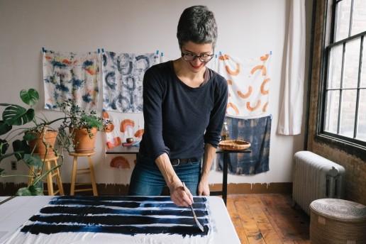 A textile artist hand paints blue stripes across a white silk scarf