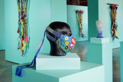 In the foreground is a beaded mask with a colorful butterfly motif placed on a black mannequin head form. In the background on three different walls that are turquoise green hang large, colorful, knotted rope works. In the midground to the right is a beaded sculpture with blue and white circular motifs that rests on a turquoise green pedestal.
